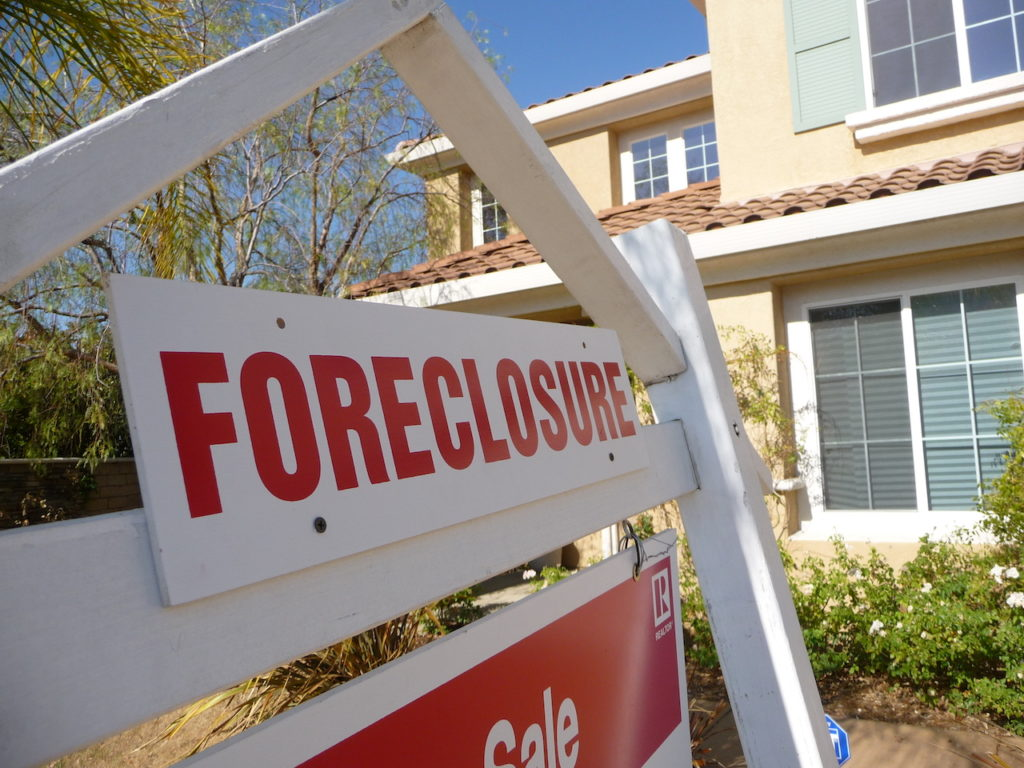 foreclosure sign in front of house