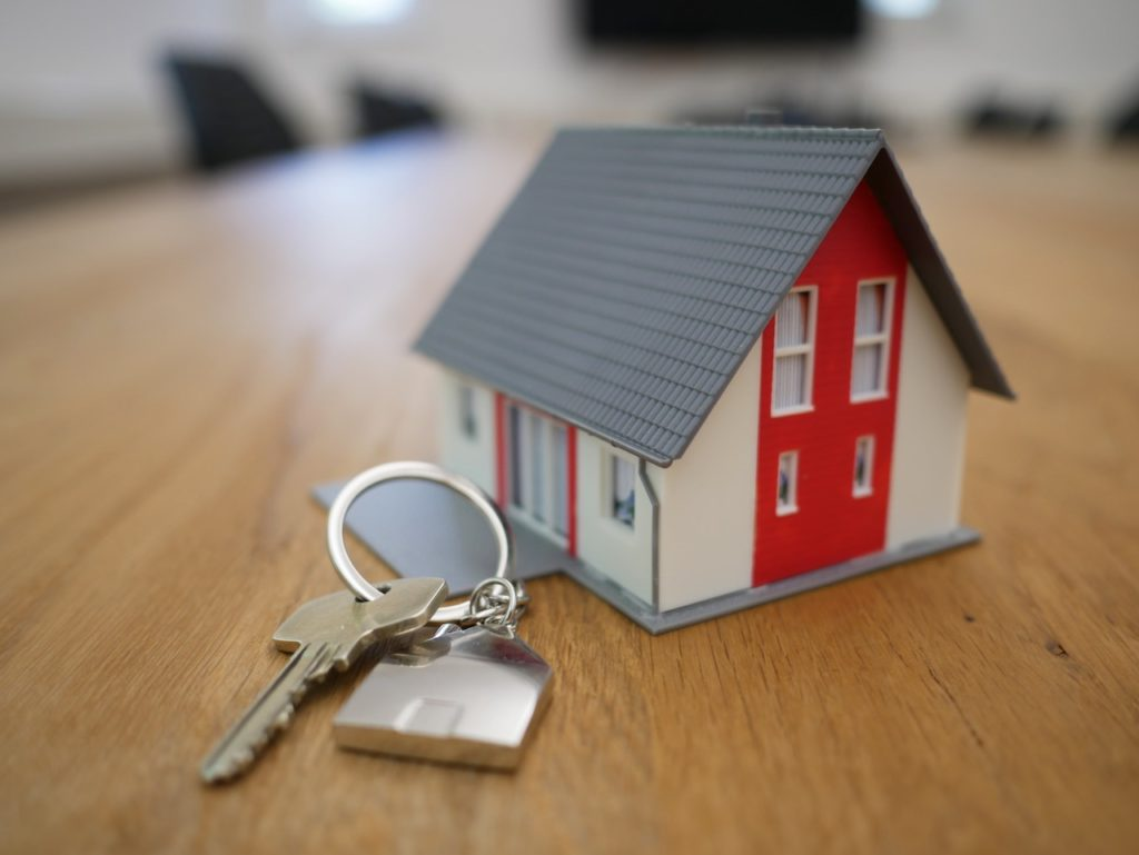 miniature house with key on a table, representing selling a house