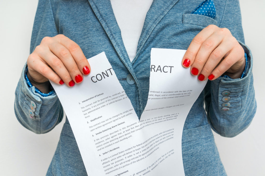 "a woman with red fingernails rips a paper titled ""contract"""