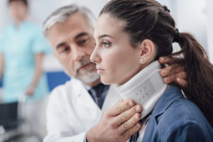 doctor fits woman's neck with a neck brace