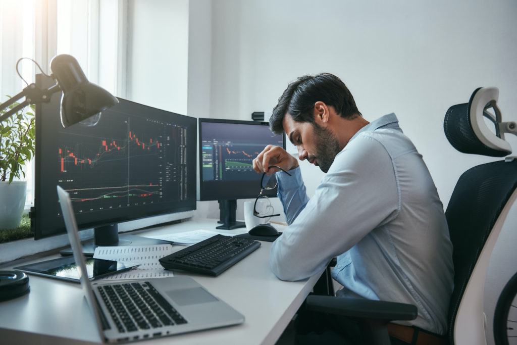 man sits in front of two computer screens showing graphs of debts and assets as he contemplates bankruptcy due to covid-19