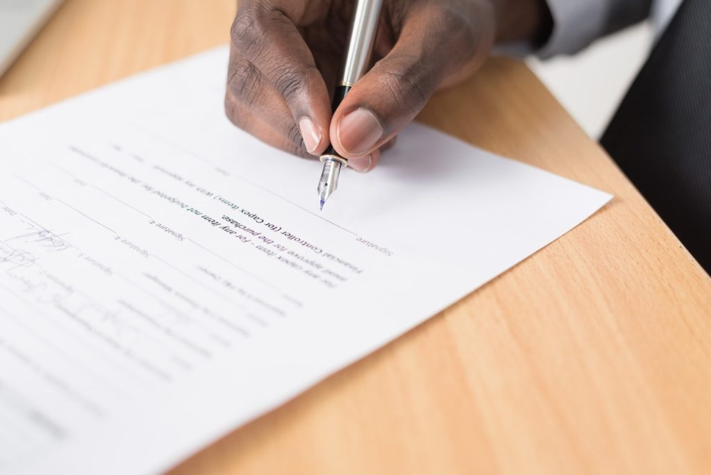 man signing housing contract