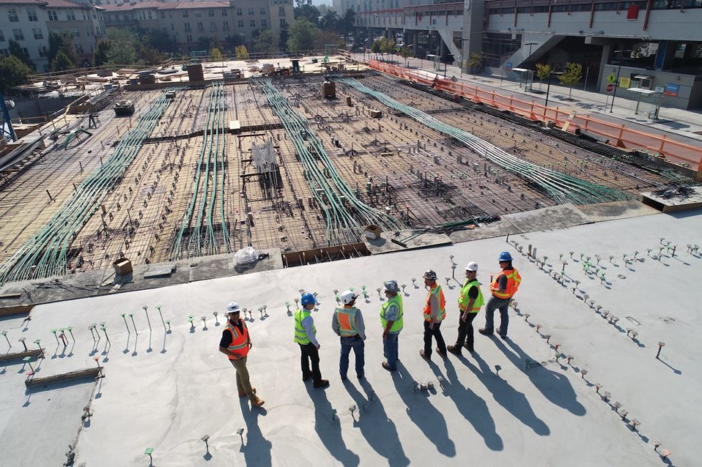 Seven construction men overlooking an empty site