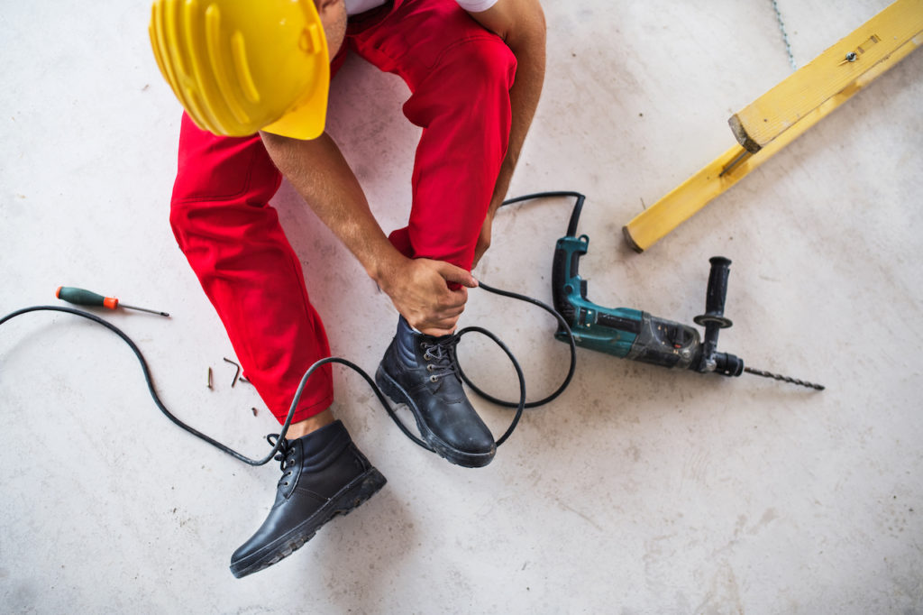 construction worker holding ankle - construction injury attorney