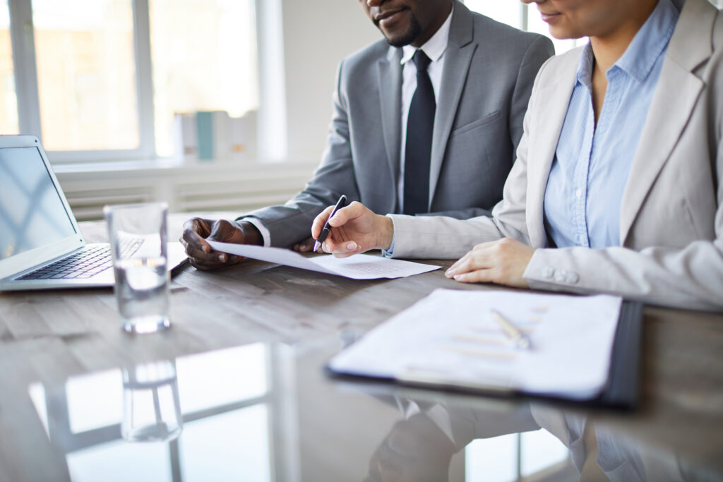 couple signs forms at table for loan modification - Riverside loan modification attorney